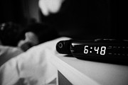 Alarm Clock Photos - Alarm Clock Early Morning With Early Twenties Woman Lying In Bed In A Bedroom by Joe Fox