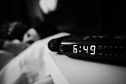 Alarm Clock Photos - Alarm Clock Early Morning With Early Twenties Woman Lying In Bed  by Joe Fox