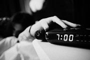 Alarm Clock Photos - Alarm Clock Early Morning With Early Twenties Woman Turning Off Alarm Lying In Bed In A Bedroom by Joe Fox