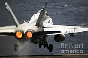Military Strike Posters - An Fa-18c Hornet Launches From Uss Poster by Stocktrek Images