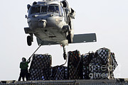 Netting Posters - An Mh-60s Sea Hawk Picks Up Supplies Poster by Stocktrek Images