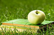 Nature Study Photo Prints - Apple on pile of books on grass Print by Michal Bednarek