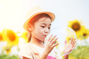 Balloon Flower Photo Metal Prints - Asian little girl is blowing a soap bubbles in sunflower garden Metal Print by Anek Suwannaphoom