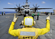 View Over Framed Prints - Aviation Boatswains Mate Directs A C-2a Framed Print by Stocktrek Images