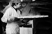 Berlin Germany Prints - Baker removing tray of bread with steam rising from an outdoor wooden baking oven on a stall at the christmas market Berlin Germany Print by Joe Fox