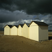 Sandy Beaches Prints - Beach huts under a stormy sky in Normandy. France. Europe Print by Bernard Jaubert