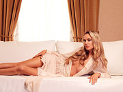 Drapery Photo Prints - Beautiful sexy woman with blond hair lying on sofa Print by Oleksiy Maksymenko