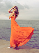Fluttering Posters - Beautiful Woman in Orange dress on Sea Shore Poster by Oleksiy Maksymenko