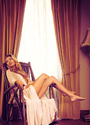 Drapery Photo Prints - Beautiful young woman in a rocking chair by the window Print by Oleksiy Maksymenko
