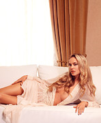 Drapery Photo Prints - Beautiful young woman with long blond hair lying on white sofa Print by Oleksiy Maksymenko