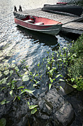 Rowboat Photos - Boat at dock on lake by Elena Elisseeva