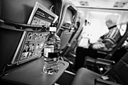 Passenger Plane Framed Prints - Bottle Of Water On Tray Table Interior Of Jet2 Aircraft Passenger Cabin In Flight Framed Print by Joe Fox