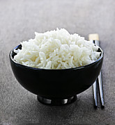 Dishes Posters - Bowl of rice with chopsticks Poster by Elena Elisseeva
