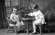 Wicker Furniture Posters - Boy Pours Sister A Cup Of Tea Poster by Underwood Archives