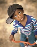 African-americans Prints - Boy Wearing Over Sized Hat Riding Bike Print by Ron Nickel