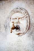 Dripping Tap Prints - Brass water faucet and carved stone face on wall Print by Stephan Pietzko