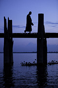 Backlit Prints - Buddhist monk walking over U Beins bridge at dusk Print by Ruben Vicente