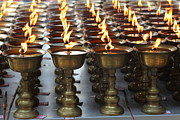 Candelabrum Framed Prints - Candles burning in a Buddhist temple. Framed Print by Luigi Camassa