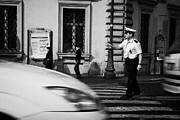 Police Officer Framed Prints - car drives across crossing as Roman Municipal policeman directs traffic at a pedestrian crossing in the Via Teatro Marcello Rome Lazio Italy Framed Print by Joe Fox