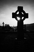 Celts Art - Celtic Cross Silhouetted At Sunset With Sun Shining Through Gap In Graveyard Donegal Ireland Irish by Joe Fox
