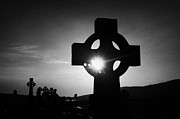 Celts Prints - Celtic Cross Silhouetted At Sunset With Sun Shining Through Gap In Graveyard Donegal Ireland Print by Joe Fox