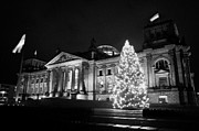 christmas tree and german flag flying fluttering on flagpole outside reichstag building Berlin Germany Print by Joe Fox