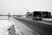 Winter Roads Posters - cleared salted gritted road in commercial district of Saskatoon Saskatchewan Canada Poster by Joe Fox