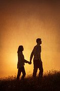 Woman In Summer Meadow Posters - Couple Holding Hands At Sunset Poster by Lee Avison