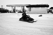 Sask Prints - couple on a snowmobile leaving a gas station Kamsack Saskatchewan Canada Print by Joe Fox