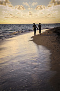Tropical Sunset Framed Prints - Couple walking on a beach Framed Print by Elena Elisseeva