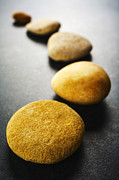 Stepping Prints - Curving Line of Brown Pebbles on Dark Background Print by Colin and Linda McKie