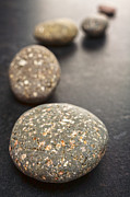 Grey Photo Framed Prints - Curving Line of Speckled Grey Pebbles on Dark Background Framed Print by Colin and Linda McKie