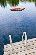 Pier Posters - Dock on calm lake in cottage country Poster by Elena Elisseeva