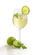 Sparkling Wine Posters - Drink with lime and mint in a wine glass Poster by Palatia Photo