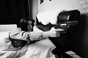 Bedside Table Posters - Early Twenties Woman Frightened Pointing Handgun Towards Door In Bed In A Bedroom Poster by Joe Fox