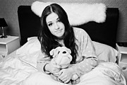 Toy Dog Photo Posters - Early Twenties Woman Holding Cuddly Dog Soft Toy In Bed In A Bedroom Poster by Joe Fox