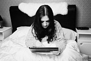 In Bed Photo Prints - Early Twenties Woman Using Tablet Computer In Bed In A Bedroom Print by Joe Fox
