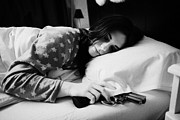 Early Twenties Woman With Hand On Handgun Under Pillow At Night In Bed In A Bedroom Print by Joe Fox