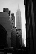 Manhaten Framed Prints - empire state building shrouded in mist in amongst dark cold buildings on 33rd Street new york city Framed Print by Joe Fox