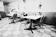 Empty Chairs Prints - empty tables in a small rural diner cafe in a town Saskatchewan Canada Print by Joe Fox