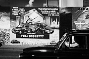 Murals Photo Prints - Falls road black taxi driving past the International wall murals in the republican falls road area of west belfast Northern Ireland Print by Joe Fox