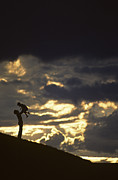Raising Art - Father holding daughter above his head along hillside silhouette by Jim Corwin