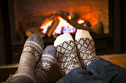 Flames Posters - Feet warming by fireplace Poster by Elena Elisseeva