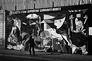 Murals Photo Prints - female tourist examines the guernica commemoration mural part of the International wall murals in the republican falls road area of west belfast Northern Ireland Print by Joe Fox