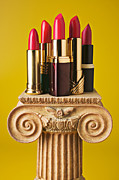 Grooming Art - Five red lipstick tubes on pedestal by Garry Gay