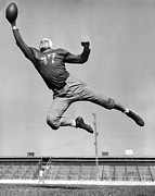 College Sports Prints - Football Player Catching Pass Print by Underwood Archives