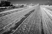 Harsh Conditions Prints - frozen salt and grit covered rural small road in Forget Saskatchewan Canada Print by Joe Fox