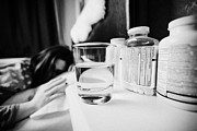 Bedside Table Posters - Glass Of Water And Bottles Of Pills On Bedside Table Of Early Twenties Woman In Bed In A Bedroom Poster by Joe Fox