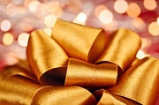 Ribbons Prints - Gold gift bow with festive lights Print by Elena Elisseeva