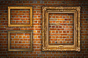 Photo Album Framed Prints - Golden frames on brick wall Framed Print by Antony McAulay